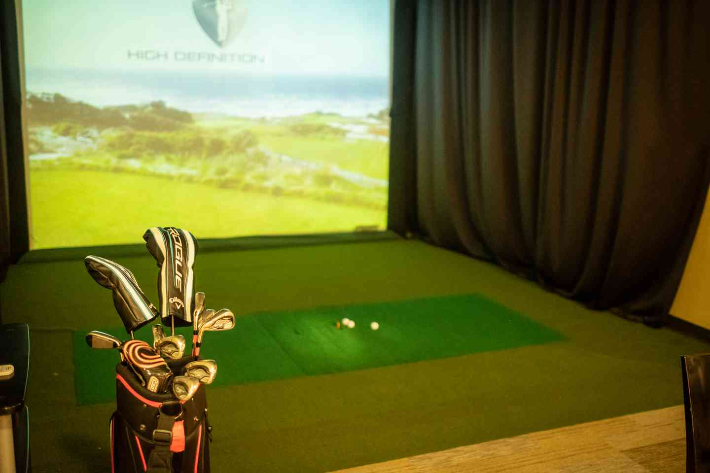 Golf clubs sitting with the golf simulator
