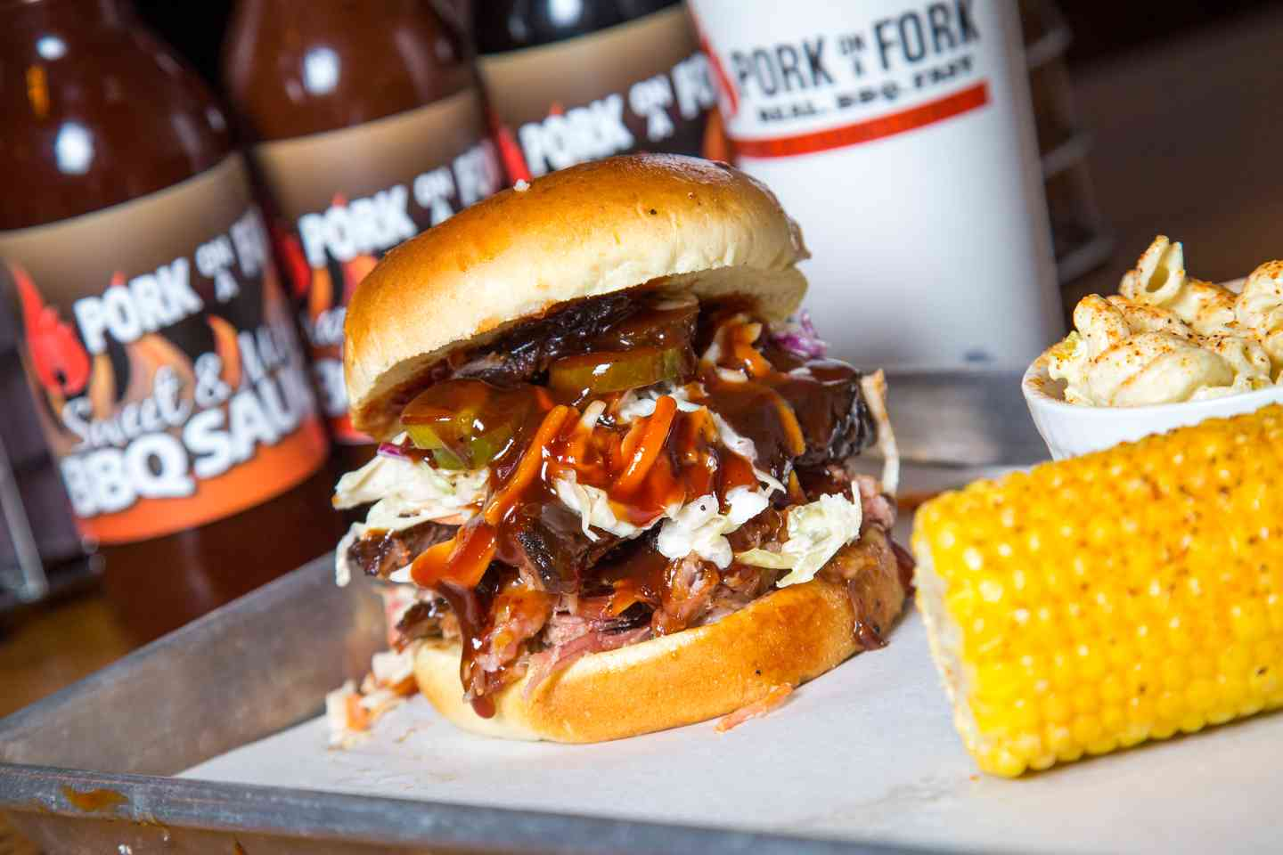 bbq pork sandwich with cole slaw and corn side