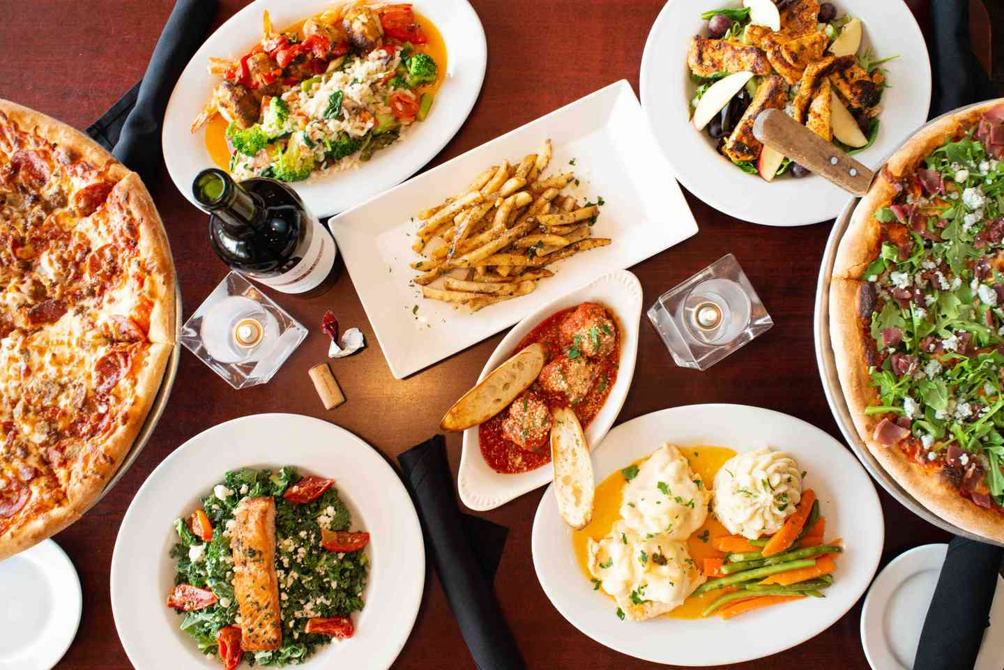 overhead shot of several plates of appetizers and pizza