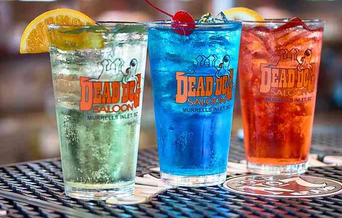Three different drinks in Dead Dog Saloon labeled glasses