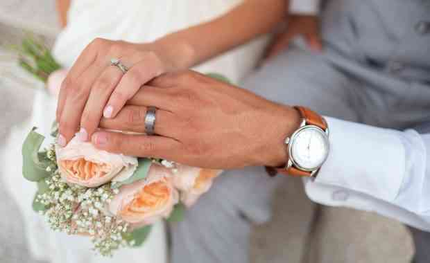 Brides hand over a grooms laying on a rose bouquet.