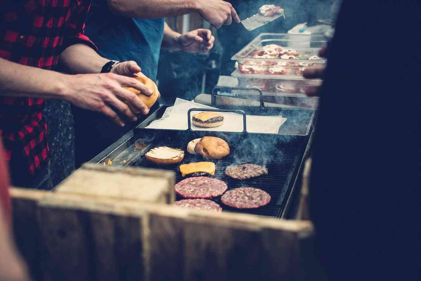 person making burgers on grill