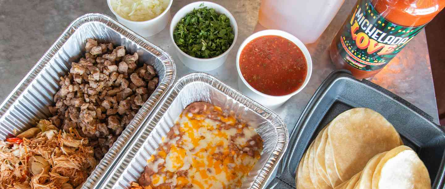 Taco catering pack with trays of meat, rice, beans tortillas and salsa
