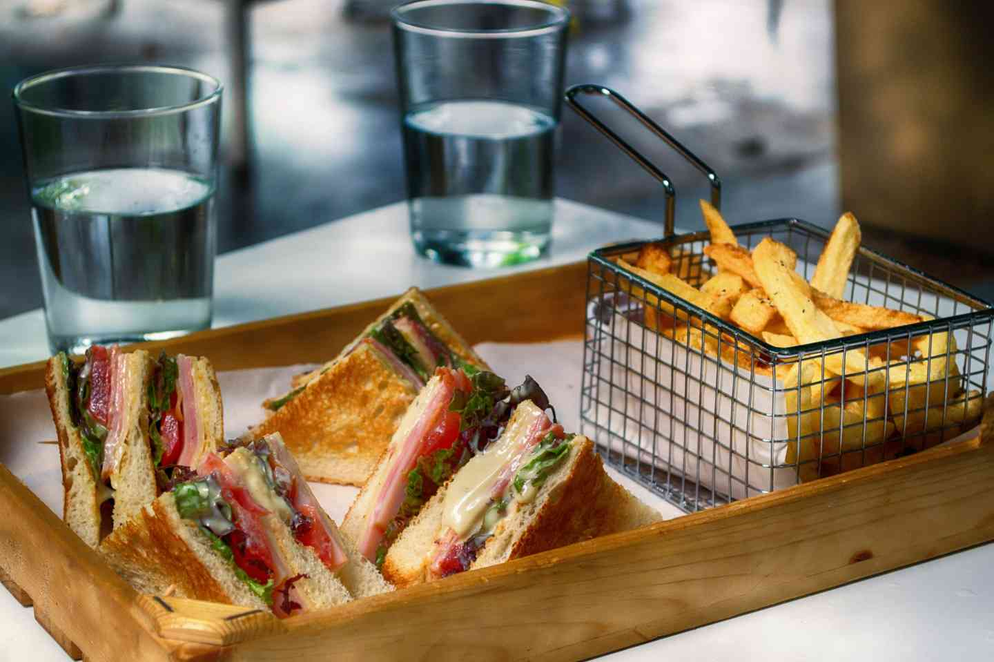 Wooden tray with a variety of sandwiches and a metal serving fry basket of fries