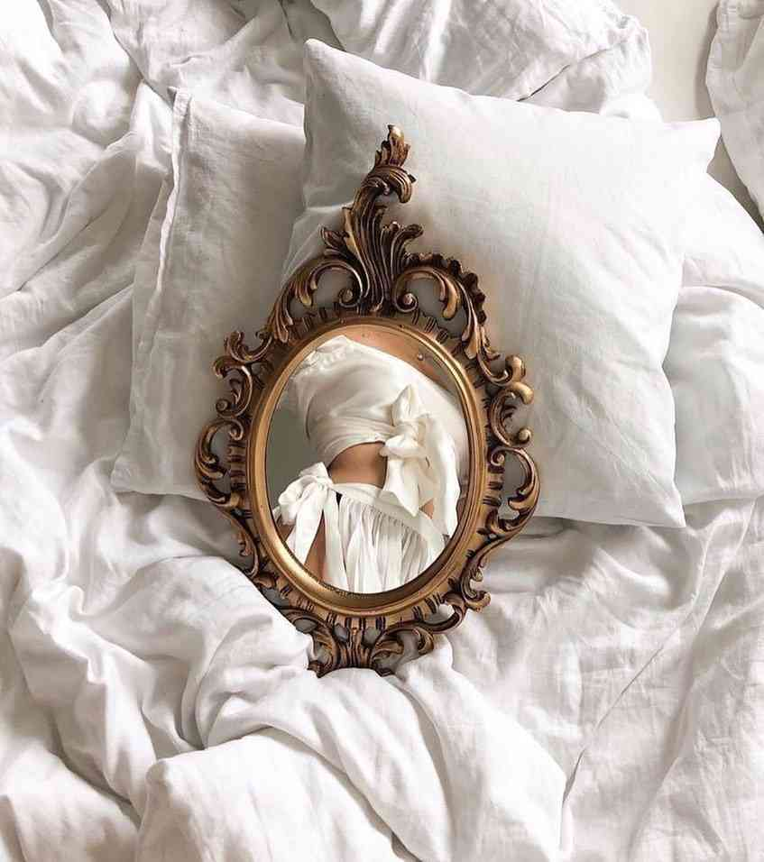 Mirror on bed reflecting girl's body