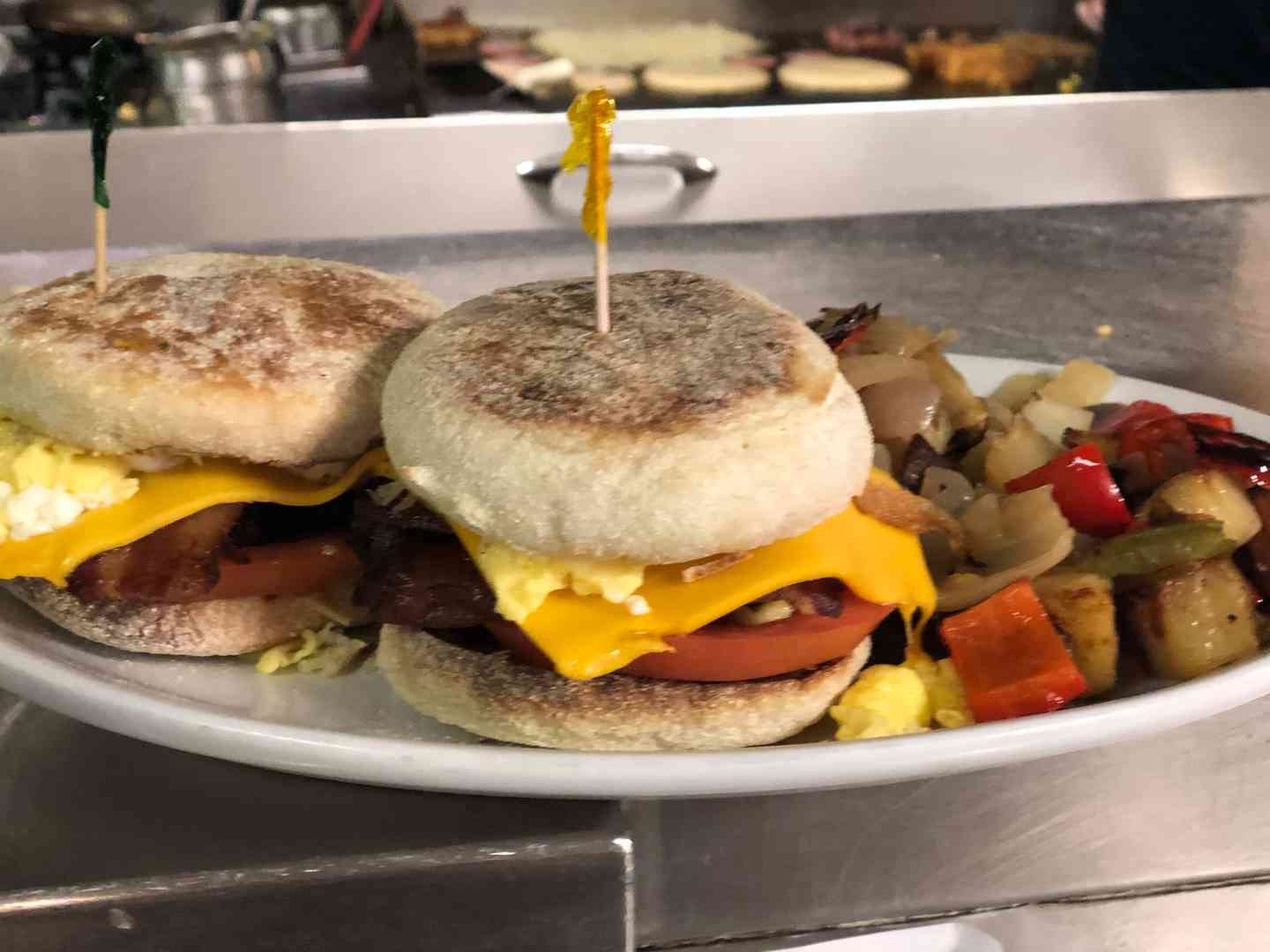 Toasted English muffin breakfast sandwich with American cheese, tomato, bacon & sausage