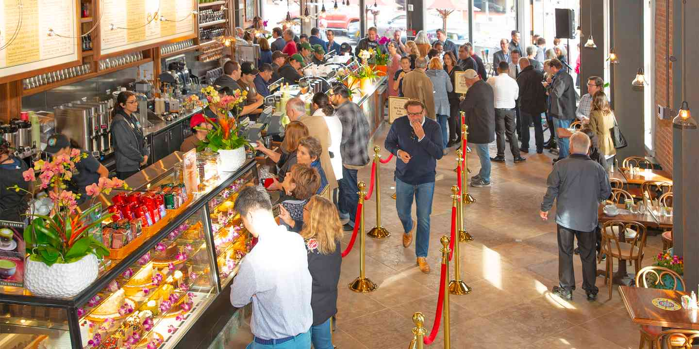 Guests waiting in line to order next to the pastry display cases at Urth Orange