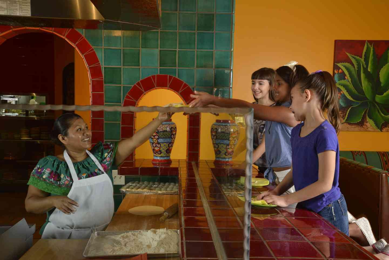 woman handing out tortillas
