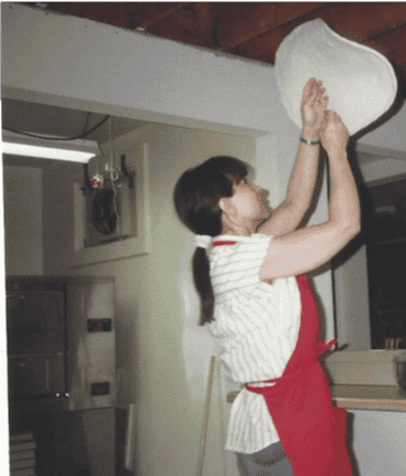 Gloria Smith tossing dough