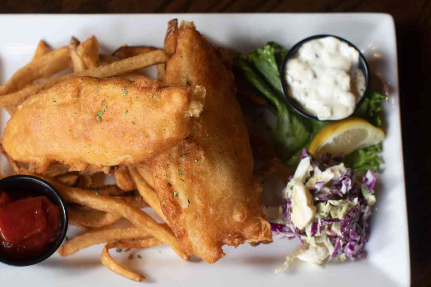 Fish and chips with coleslaw and a lemon wedge