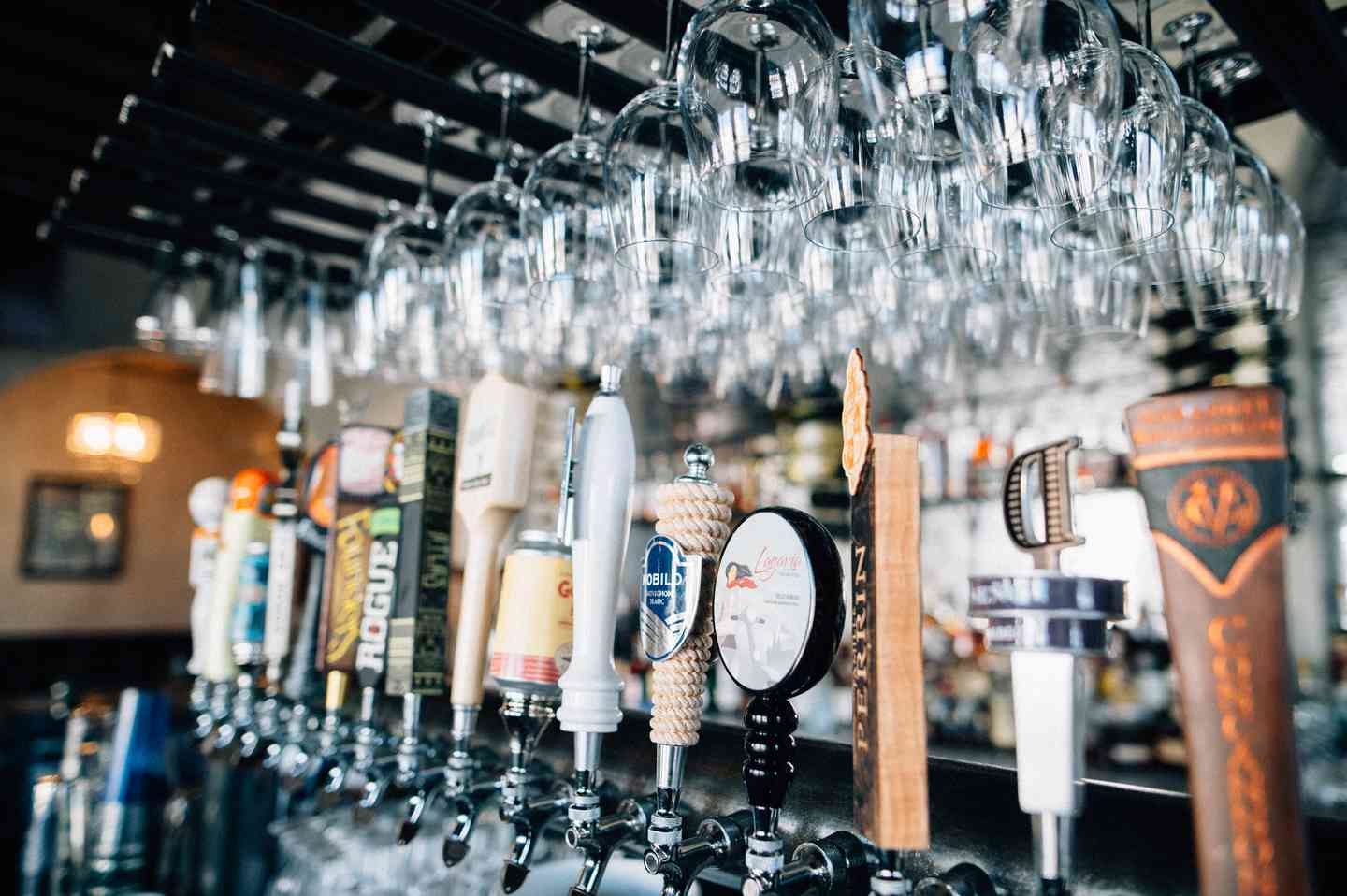 Variety of beers on tap with wine glasses hanging above on a wine rack.