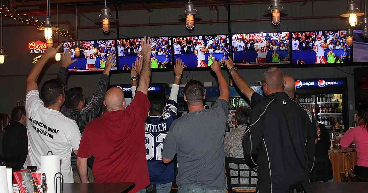 crowd at bar watching football game on overhead tvs
