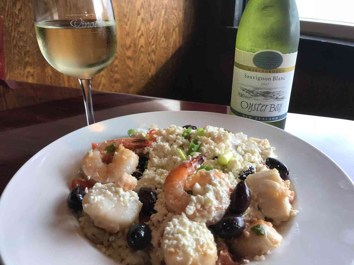 Shrimp dinner with a glass of wine and wine bottle