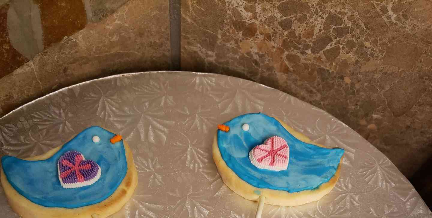 Cookies in the shapes of blue birds with hearts for wings