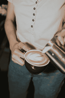 person pouring latte