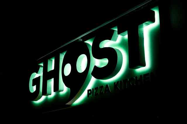 ghost pizza kitchen exterior sign at night