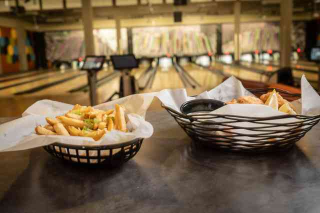 Fries sitting on a table with a bowling alley in the background