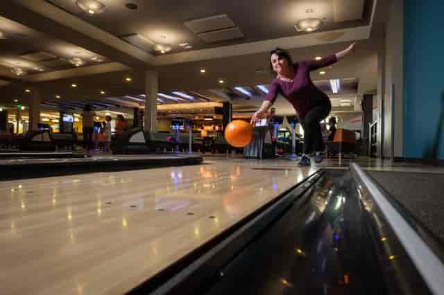 Woman in a purple shirt throwing an orange bowling ball down a lane.