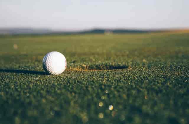Golf ball sitting on golfing green near hole