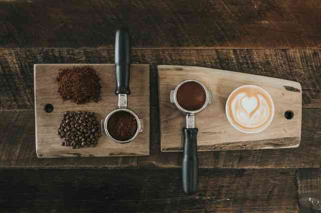 Coffee beans, ground coffee and a cup of coffee with a decorative creamer heart