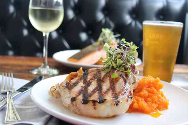 Porkchop with grill marks, glass of beer and a glass of white wine