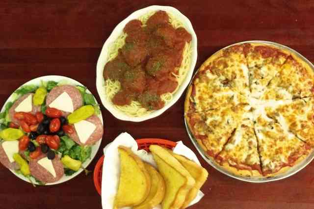 family meal with salad, spaghetti and meatballs, pizza and bread