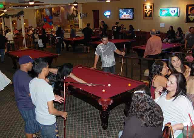 several groups of people shooting pool