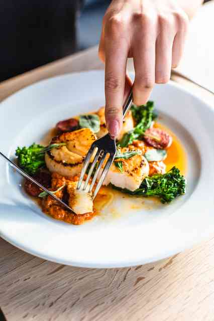 person cutting scallop on plate