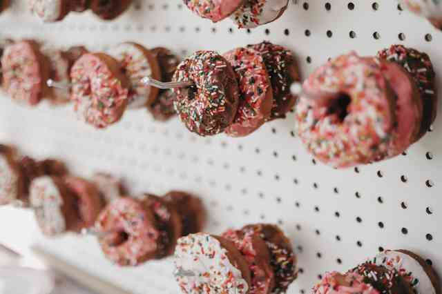 Pink and chocolate sprinkled donuts hanging on cork board hooks.
