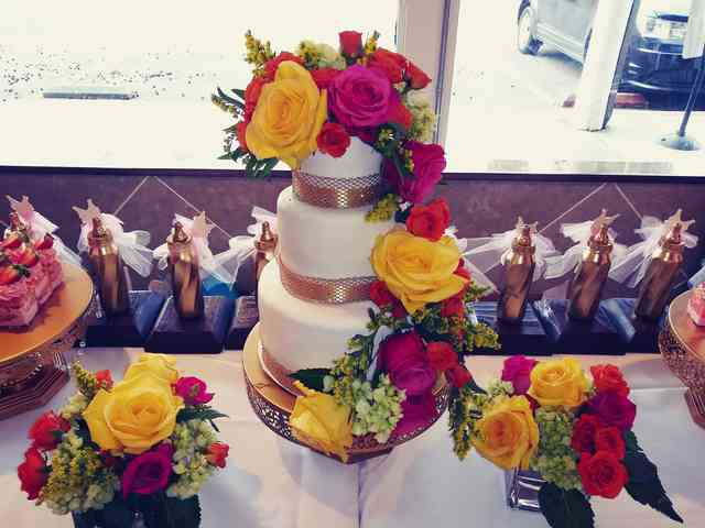 White three tier wedding cake decorated with brightly colored flowers