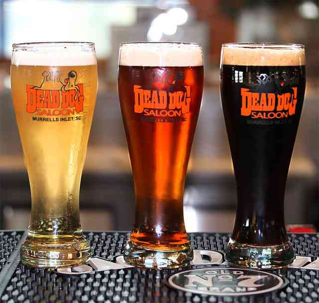 Three beers in long glasses with Dead Dog Saloon logo on them