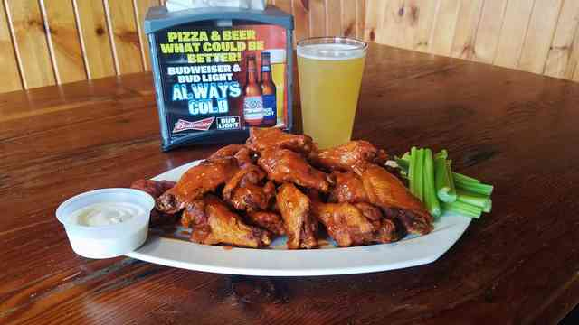 Chicken wings with celery, dressing and beer.