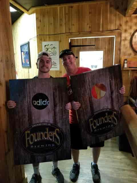 men holding cornhole boards
