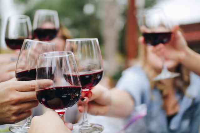 Friends sharing a glass of red wine