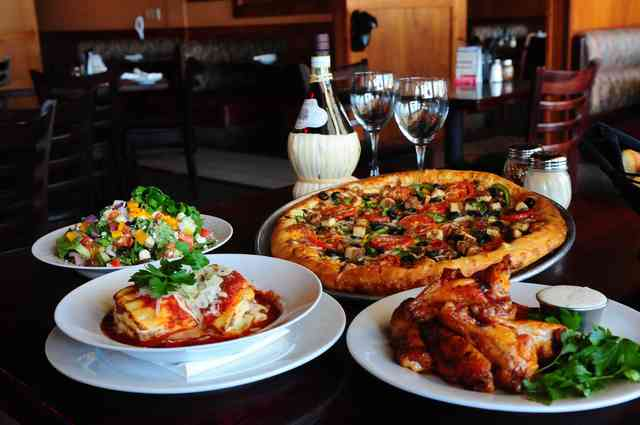 table with pizza, lasagna, salad and wings