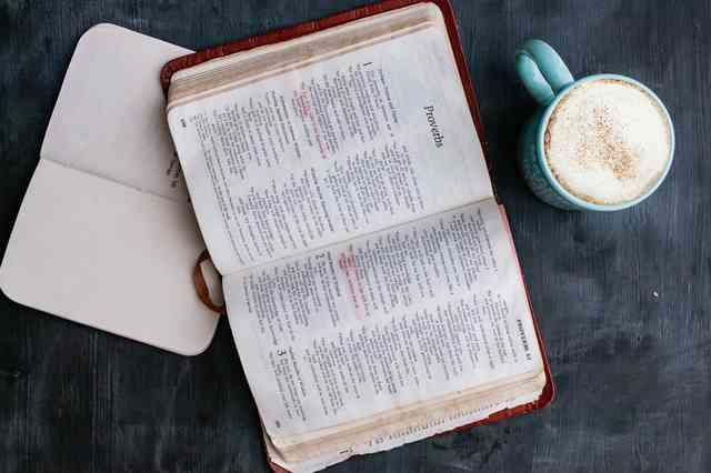 Bible open to Proverbs with a mug of coffee