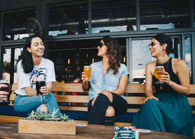 three women sitting on a bench