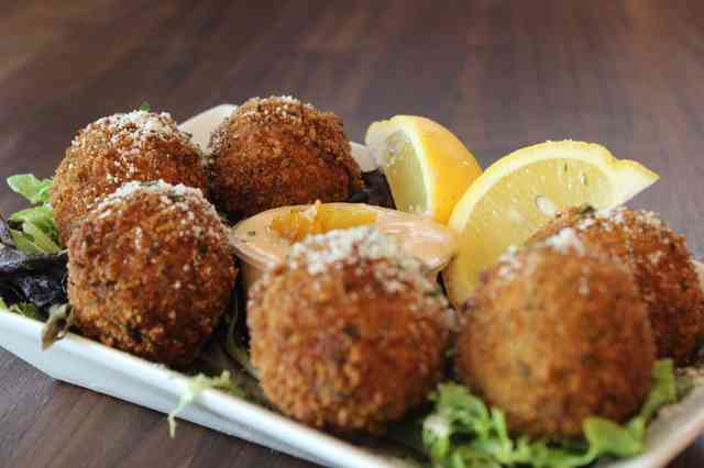 Plate of six meatballs with lemon slices