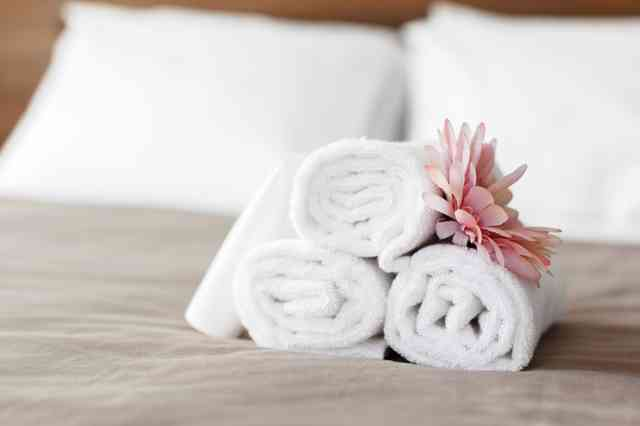 Towels and flower on a bed