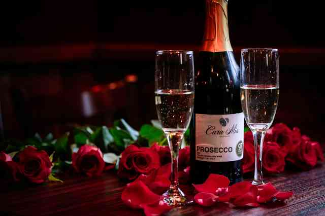 a bottle of sparkling wine with 2 glasses and roses