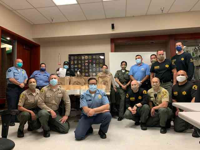 Group photo of West Hollywood Sheriffs in room at station wearing masks.