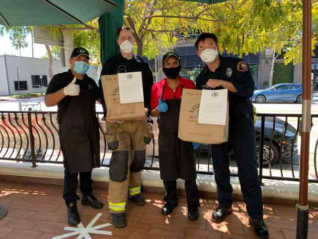 2 Urth Melrose employees with 2 Firemen holding Urth shopping bags and