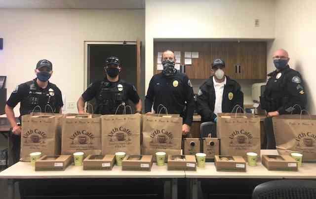 Five Laguna Beach police officers standing behind long table with brown Urth bags and lunch boxes