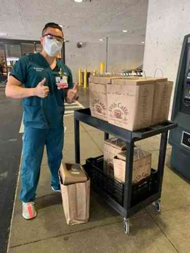 Male nurse with mask giving thumbs up standing next to a cart full of Urth food bags.