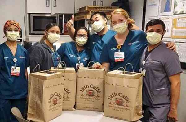Group of six nurses and doctors wearing masks and blue scrubs standing behind 4 large Urth food bags on table. Male nurse in background is giving thumbs up.