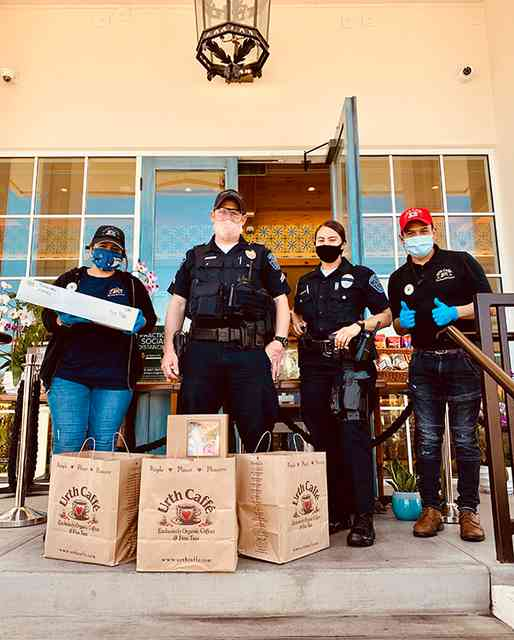 Male and Female Hawthorne Police with two Urth employees on Urth South Bay entrance with Urth bags and lunch boxes