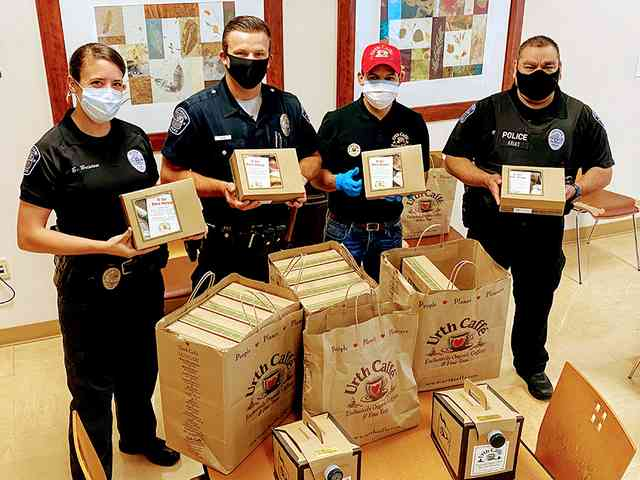 3 police and one Urth employee standing at table loaded with Urth Caffé lunch boxes