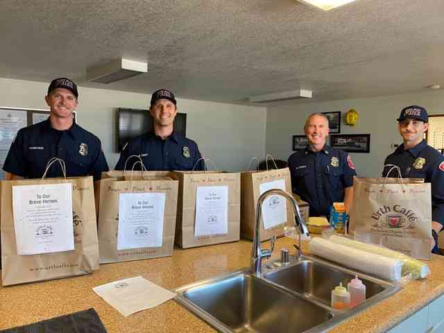 Laguna Beach firemen behind table with Urth food bags in front of them.