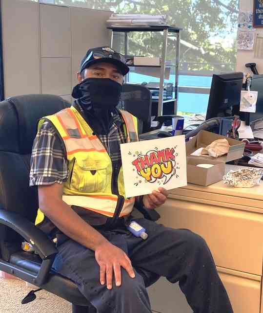 Man sitting at desk with black mask, hat, yellow vest and holding a thank you sign.