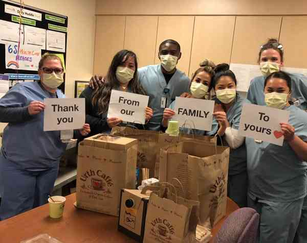 """7 White Memorial Hospital nurses with yellow masks holding four sheets of paper that say """"Thank You From our Family To Yours"""" with image of red heart. They are standing behind a table full of Urth Caffé food bags and coffee."""